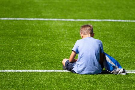 Sad alone boy with backpack sitting stadium outdoors 스톡 콘텐츠