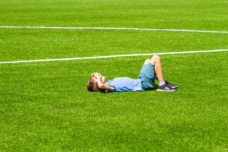 Boy lying on the football field