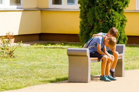 Kid comforting consoling upset sad boy in school yard Stockfoto