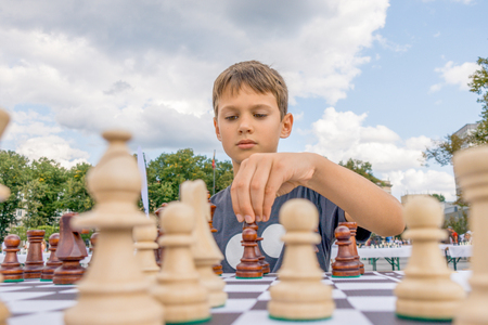 Kid playing chess at chessboard outdoors. Boy thinking hard on chess combinations Foto de archivo