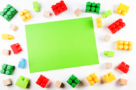 Colorful wooden cubes and plastic construction bricks with green blank paper card on white background