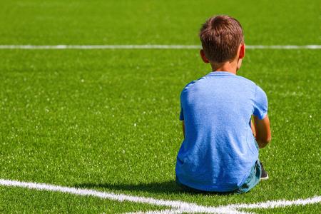 Sad alone boy sitting in soccer field stadium outdoors