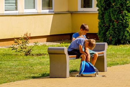 Niño reconfortante consolador molesto niño triste en el patio de la escuela