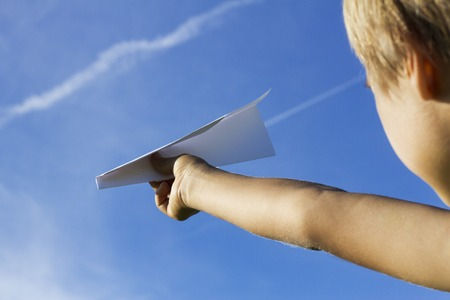 Child with paper plane against blue sky. Low angle view