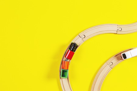 Toy trains and wooden rails on yellow and blue color background