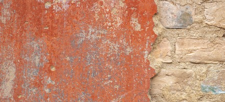 Old cracked weathered shabby red painted plastered peeled brick wall background
