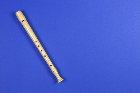 Musical instrument flute on blue color background. Stock Photo