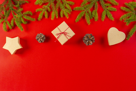 Christmas composition. Fir tree branches, pine cones and present gift boxes on red background Stock Photo
