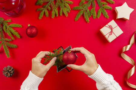 Christmas gift wrapping. Womans hands packing Christmas presents on red background