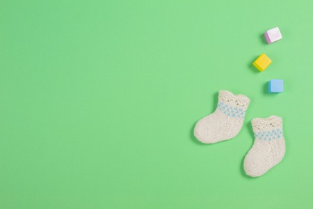 Knitted baby wool socks and wooden bricks on green background