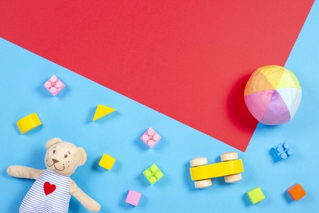 Baby kids toys background. Wooden cars, colorful bricks and soft toys on blue and red color background