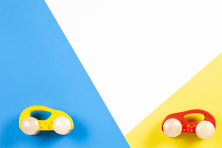 Two wooden toy cars on colorful background