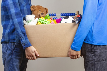 Donation concept. Kids hands holding donate box with clothes, books and toys 版權商用圖片