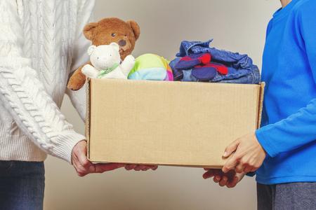Notion de don. Faire don d'une boîte avec des vêtements, des livres et des jouets dans la main des membres de la famille