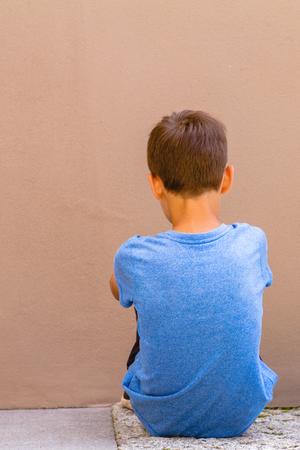 Triste niño solo sentado en el suelo detrás de la pared al aire libre