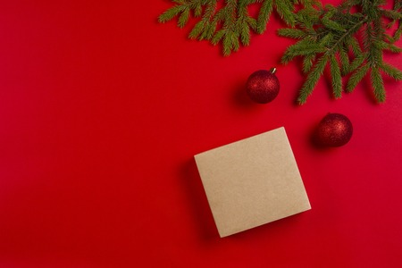 Christmas composition. Fir tree branches, christmas decorations and present gift box on red background