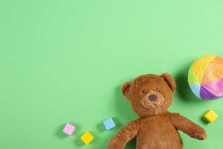 Baby kids toys background with teddy bear, wooden colorful cubes and bricks on green background