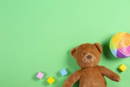 Fond de jouets pour enfants bébé avec ours en peluche, cubes colorés en bois et briques sur fond vert