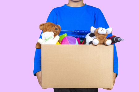 Donation concept. Kid holding donate box with clothes, books, school supplies and toys, yellow color background Stock fotó