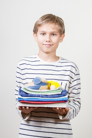 Donation concept. Kid holding in his hands books, clothes and toys for donate