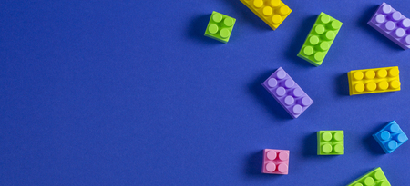 Baby kid toys background. Colorful plastic construction blocks on blue background Banque d'images - 123003612