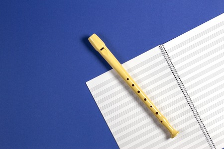 Open exercise book with pentagrams and musical instrument flute on blue background