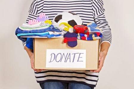 Woman hand holding donation box with clothes, toys and books for charity Stock Photo
