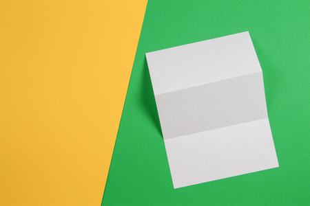 Mockup of blank white tri fold booklet brochure on green and yellow background 写真素材