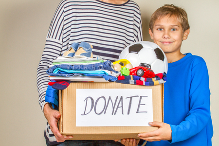 Donation concept. Donate box with clothes, books and toys in child and mother hand