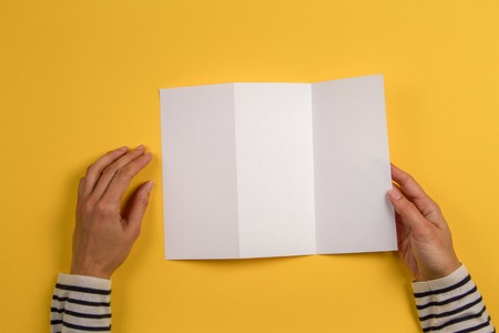 Woman hands holding blank white flyer brochure booklet. Mockup sheet template advertising booklet on yellow background