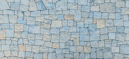 Masonry wall of stones with irregular pattern texture background
