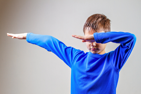 Kid throws dab on the background of a gray wall