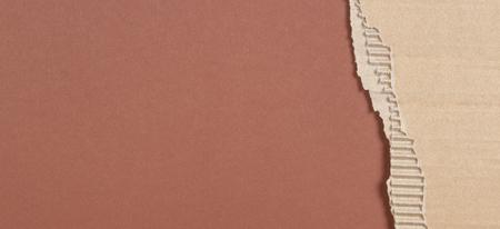 Brown corrugated cardboard ragged edge frame on brown background Stock Photo