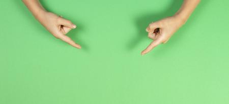 Mani dei bambini che puntano su sfondo verde pastello Archivio Fotografico