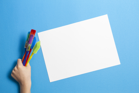 Child hand with colorful paintbrushes and blank white paper sheet on blue background