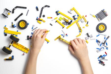 Manos de niño haciendo coche robot. Fondo robótico, aprendizaje, tecnología, educación madre para niños.