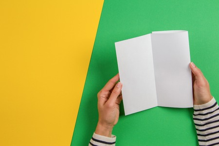 Woman hands holding blank white flyer brochure booklet. Mockup sheet template advertising booklet on green and yelow background