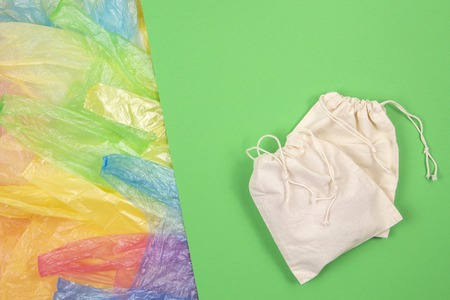 Many multicolored plastic bags with one eco natural reusable bag for shopping on green background. Zero waste, eco friendly, no plastic concept
