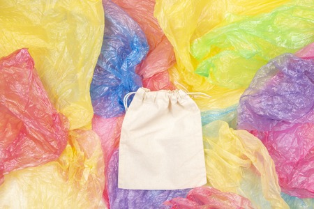 Many multicolored plastic bags with one eco natural reusable bag for shopping. Zero waste, eco friendly, no plastic concept Stok Fotoğraf
