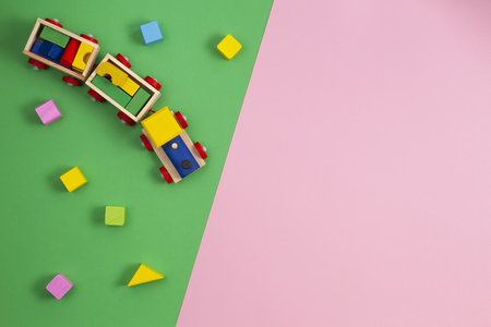 Toy background. Wooden toy train with colorful cubes on pink and green background