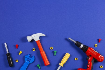 Toys background. Top view of toy tools on blue background