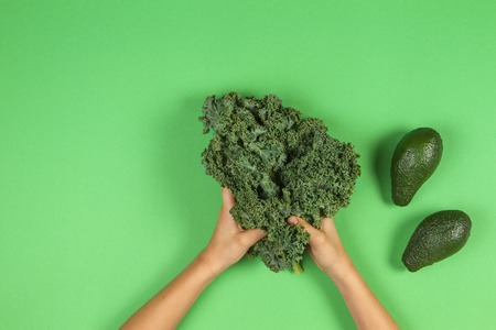 Kids hands with bunch of kale leaves and two avocados on green background. Diet, detox and healthy food concept 版權商用圖片