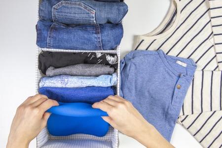 Mani della donna che mettono in ordine i vestiti dei bambini nel cestino. Stoccaggio verticale di indumenti, riordino, concetto di pulizia della stanza Archivio Fotografico
