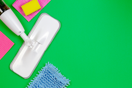 Housework, housekeeping, household, cleaning service concept. Cleaning spray mop with rags and sponges on green background