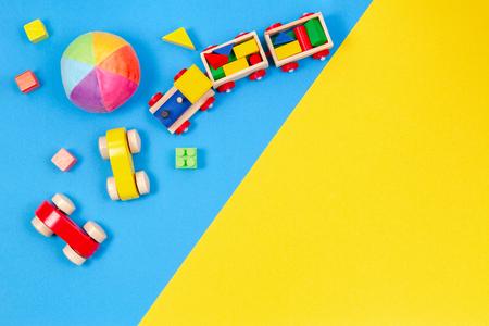 Fondo de juguetes para niños de bebé. Tren de madera, coche de juguete, bloques de colores sobre fondo azul y amarillo