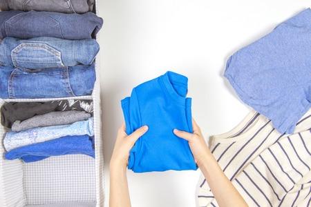 Vertikale Lagerung von Kleidung, Aufräumen, Raumreinigungskonzept. Hände, die Kinderkleidung im Korb aufräumen und sortieren.