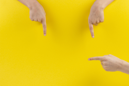 Child hands fingers pointing on yellow background