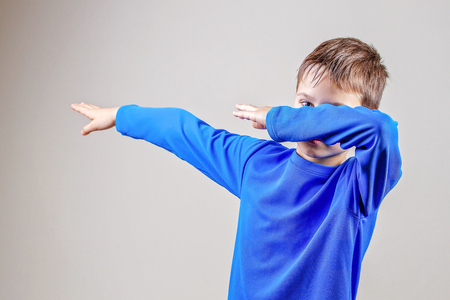 Kid throws dab on the background of a gray wall Reklamní fotografie