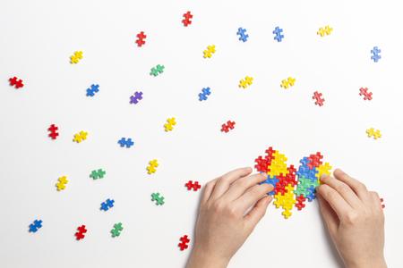 Manos de niño haciendo corazón multicolor sobre fondo blanco. Vista superior