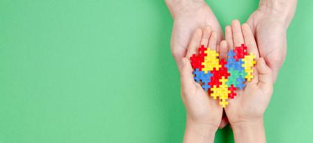 Mani del bambino e dell'adulto che tengono cuore colorato su sfondo verde. Concetto di giornata mondiale della consapevolezza dell'autismo autism